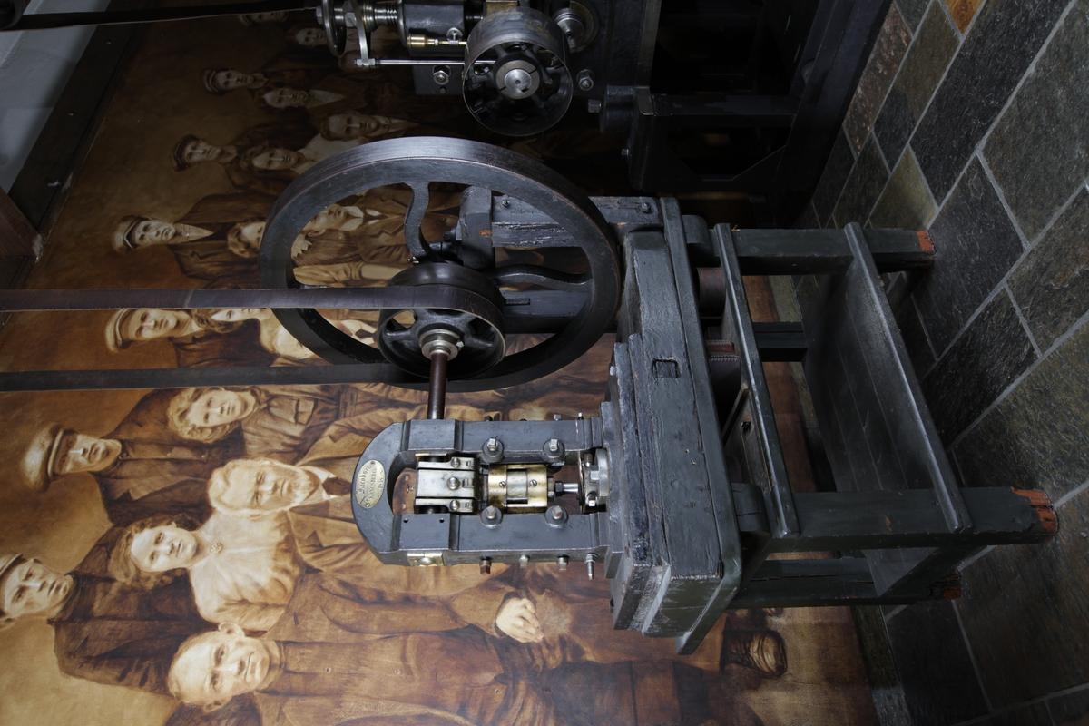 Maskin som brukes til å stanse ut rondeller / myntblanketter. Den har et stort hjul som står vertikalt på en stang som går gjennom selve pressa som stanser ut rondellene. Maskinen er montert på ett trebord.