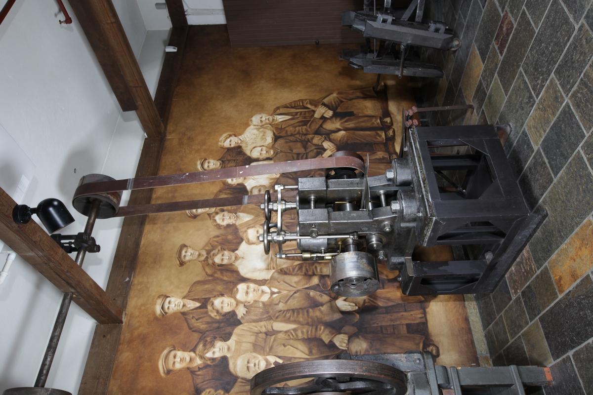 Maskinen har to firkantede vegger som er boltet fast på en plate. På tvers mellom veggene går flere sylindere i ulik størrelse, og vertikalt  gjennom hver vegg går en stor bolt med gjenger og hjul på toppen. Maskinen er av metall og er montert på en rektangulær kasse.