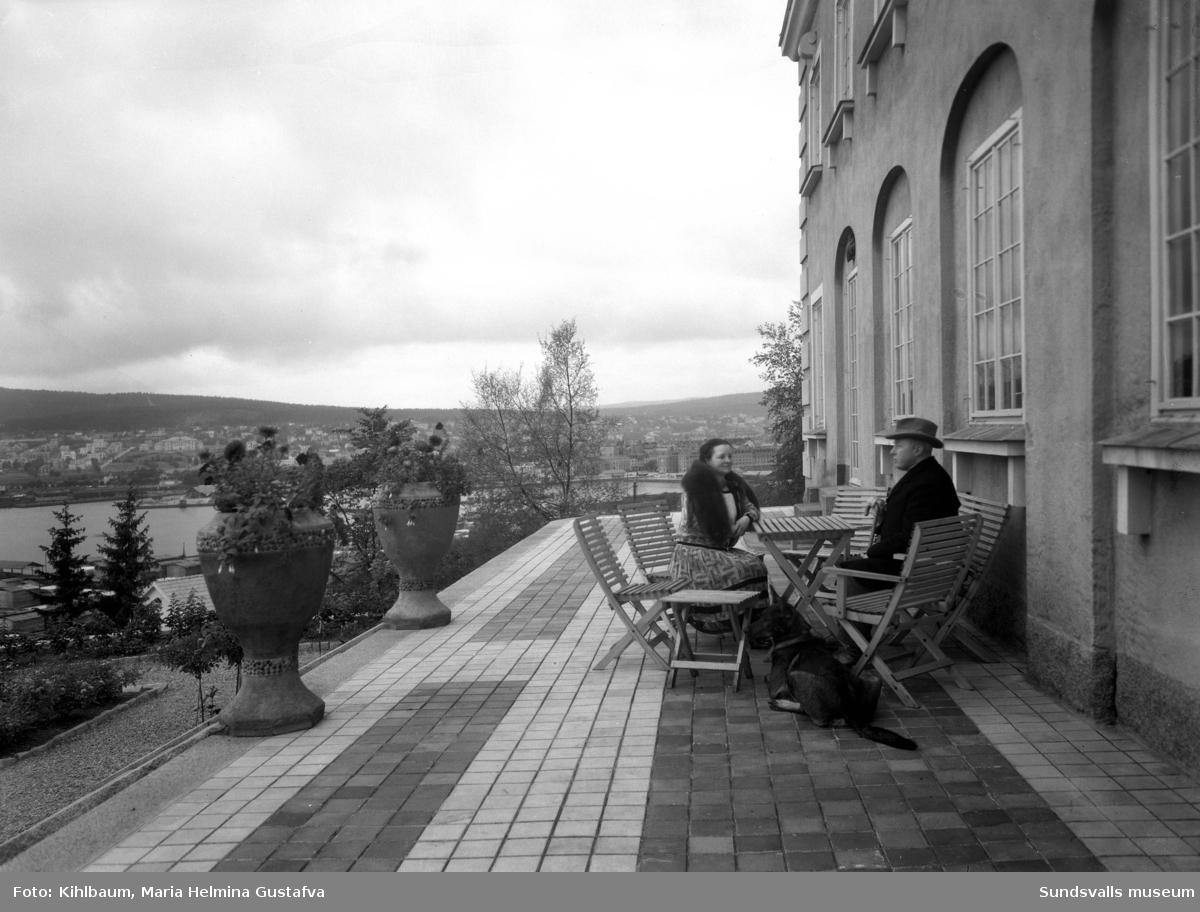 """Leonard och fru Thora Wallerstedt samt hund på altanen utanför sin bostad i Haga. Villan var tidigare kallad """"Haga slott"""" och senare Villa Wallerstedt."""