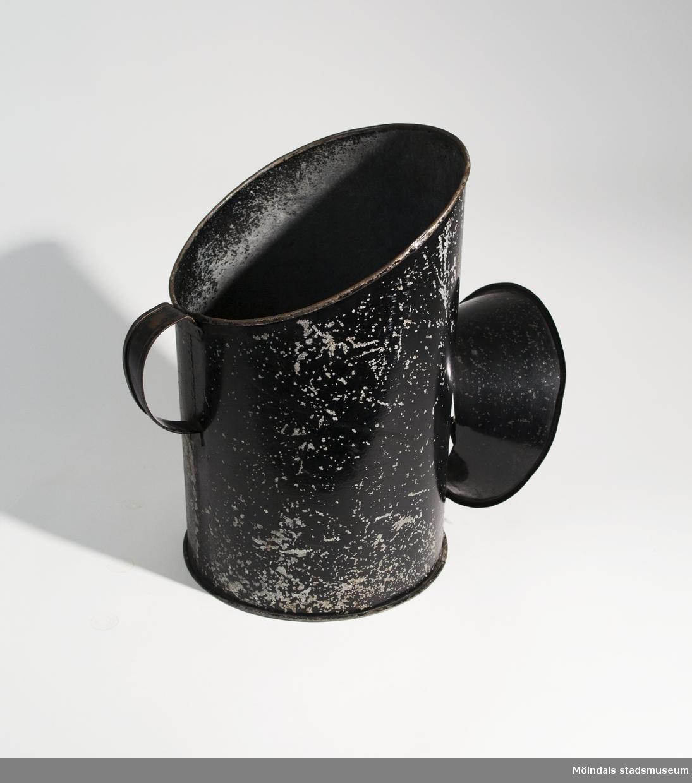 Kolbox på fot med handtag, svartmålad. Används för att bära och förvara kol för eldning i värmepanna. Avskavd färg, stort rosthål i botten.