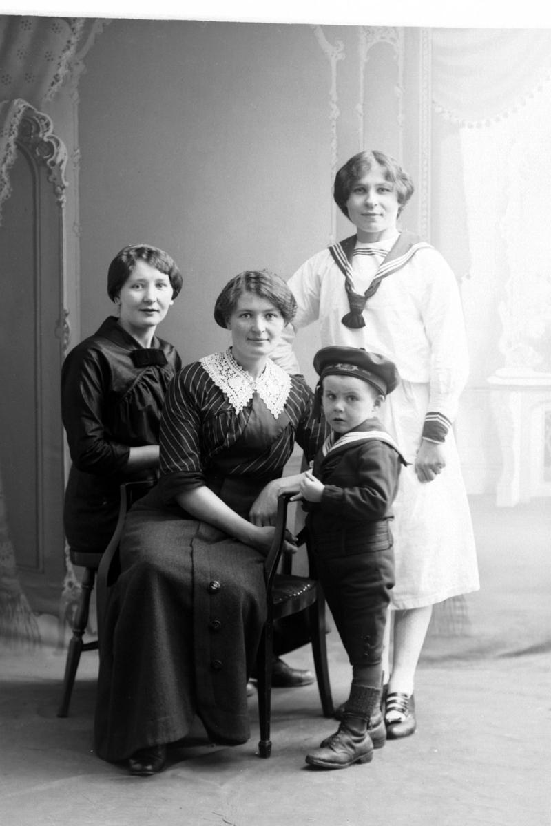 Studioportrett av tre kvinner med et barn i matrosdress.