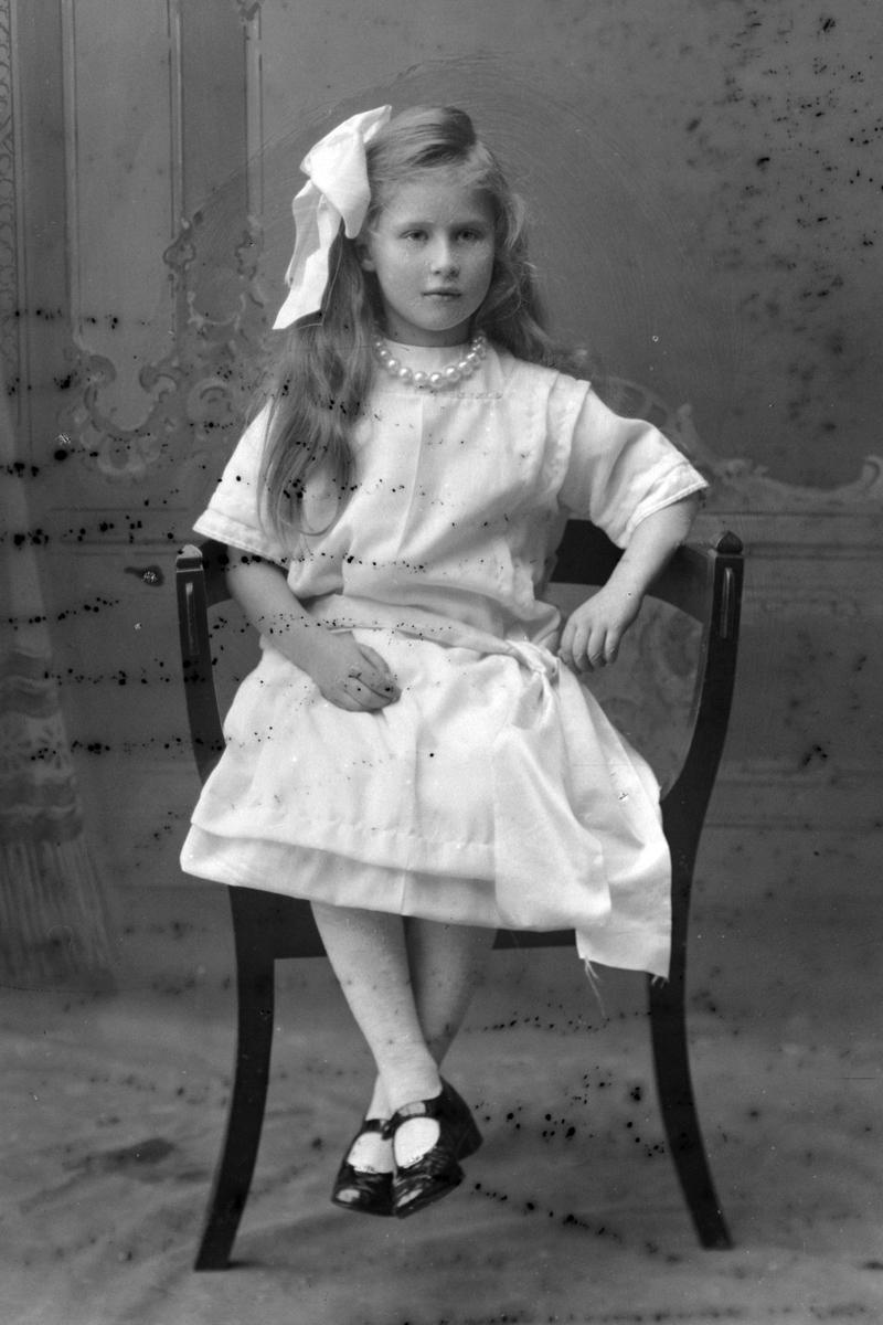 Studioportrett av ung jente på en stol.