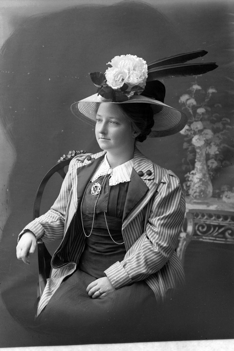 Studioportrett av en sittende kvinne med hatt med fjær og blomster.