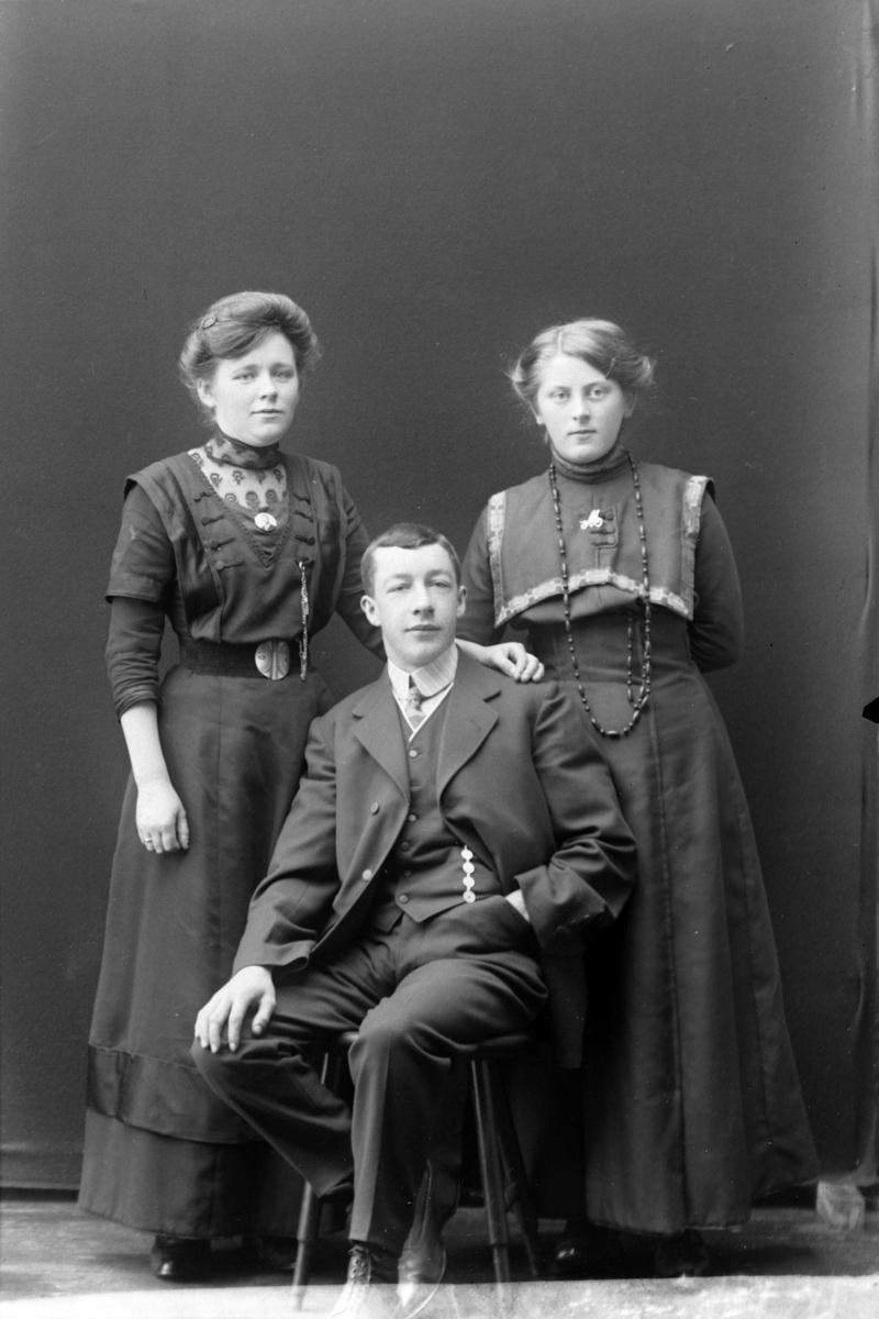 Studioportrett av en mann som sitter foran to stående kvinner.