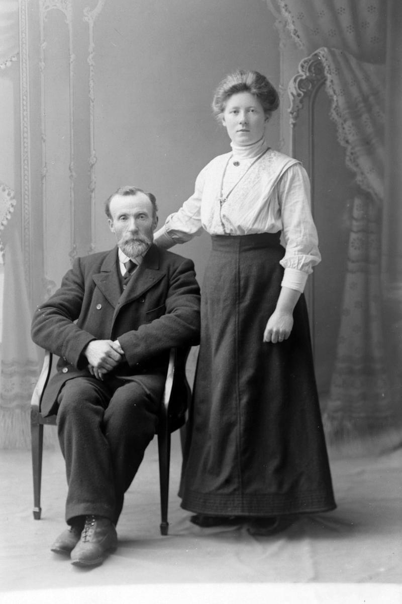 Studioportrett av en sittende mann ved siden av en stående kvinne.