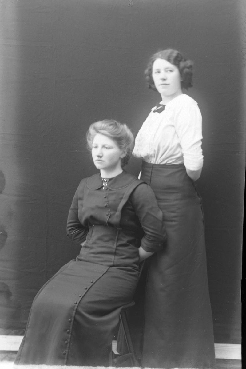 Studioportrett av to kvinner foran en mørk bakgrunn.