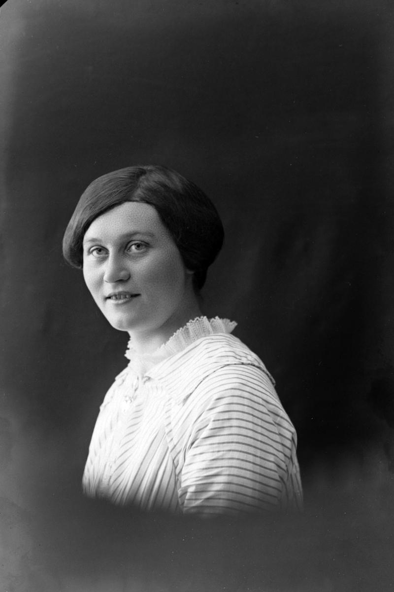 Studioportrett i halvfigur av kvinne med stripet skjorte.