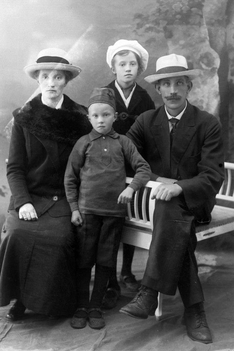 Studioportrett av en mann og kvinne med to barn.
