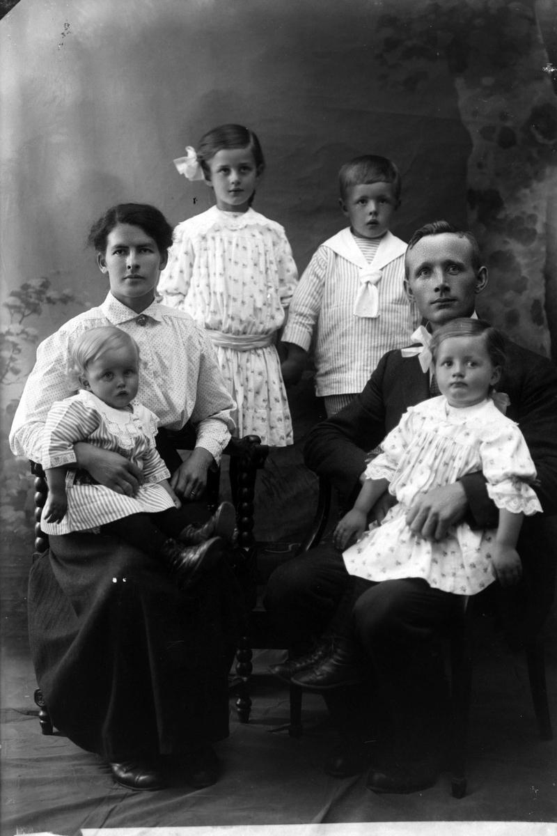 Studioportrett av en familie på seks.