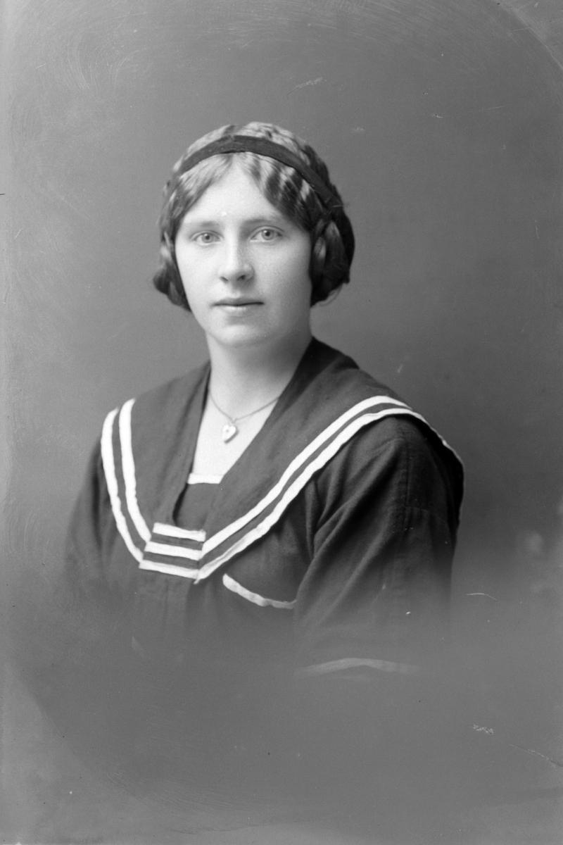 Studioportrett av en kvinne med hårband på hodet.