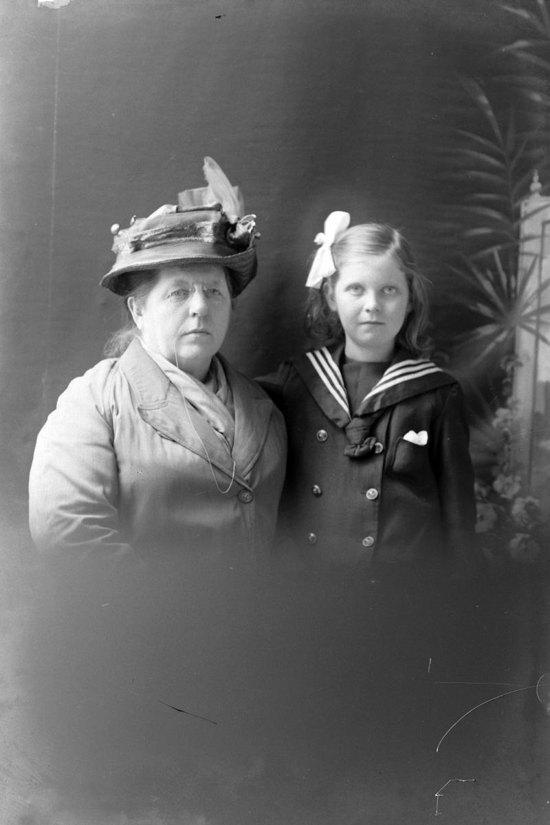 Studioportrett av en voksen kvinne ved siden av en liten jente.