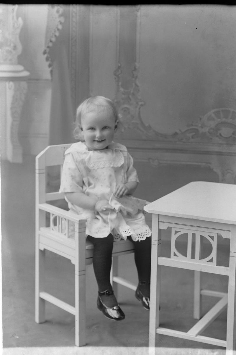 Studioportrett av et lite barn som sitter i en stol.