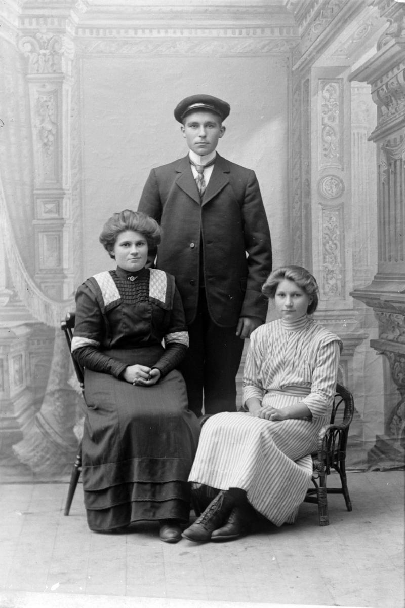Studioportrett i helfigur av en mann og to kvinner.