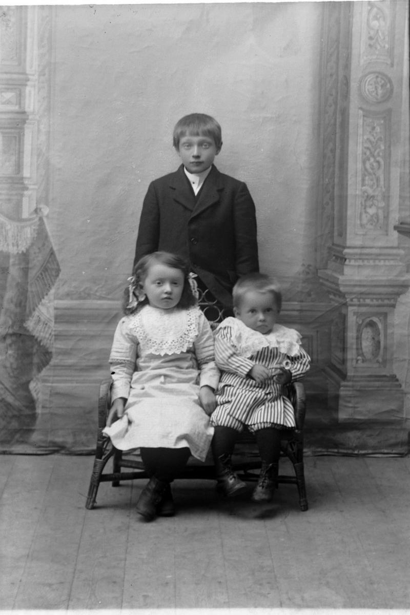 Studioportrett av tre barn i helfigur.