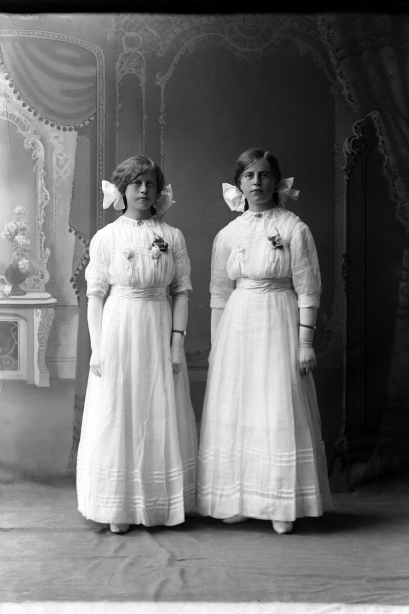 Studioportrett i helfigur av to jenter i hvite kjoler.