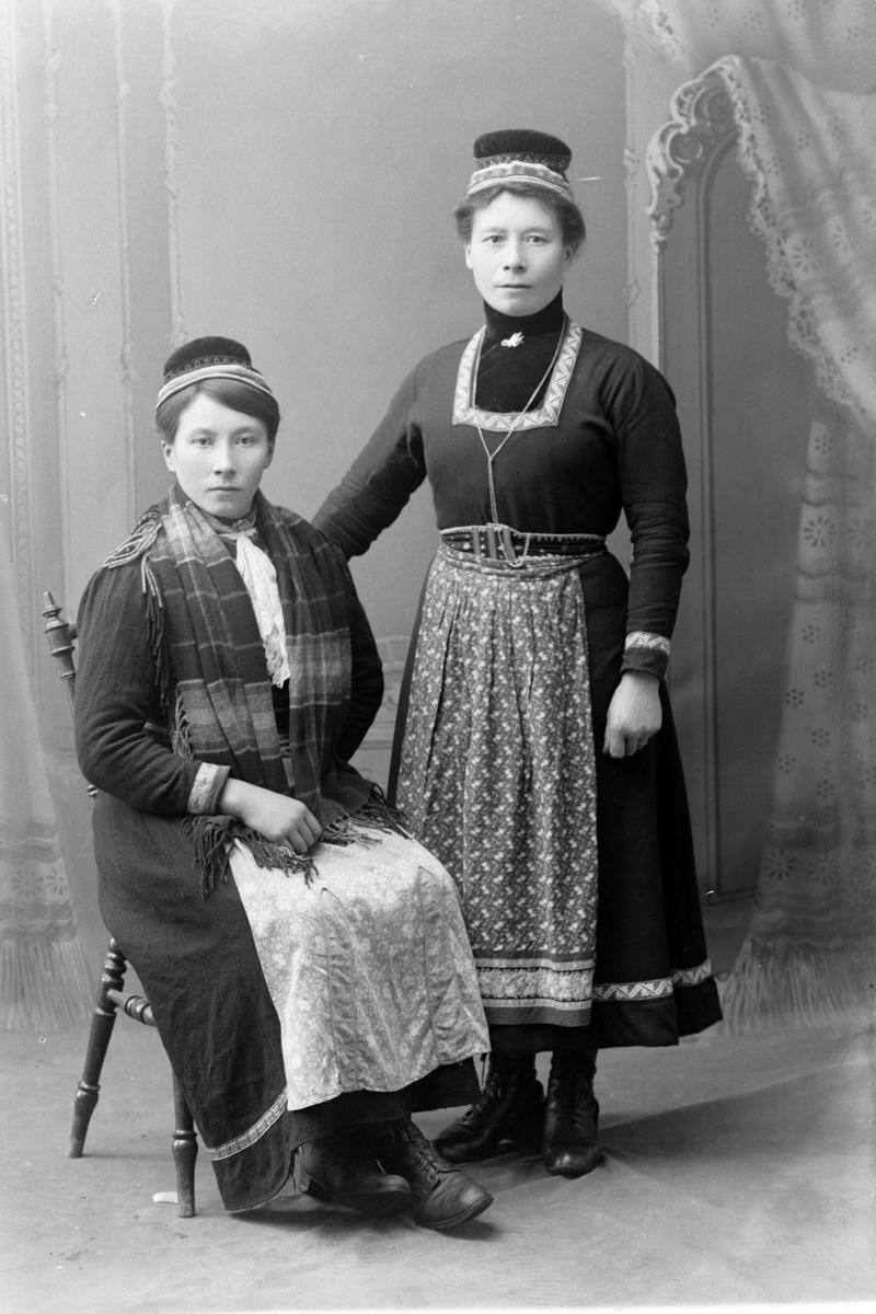 Studioportrett av to kvinner som er kledd i samiske drakter.