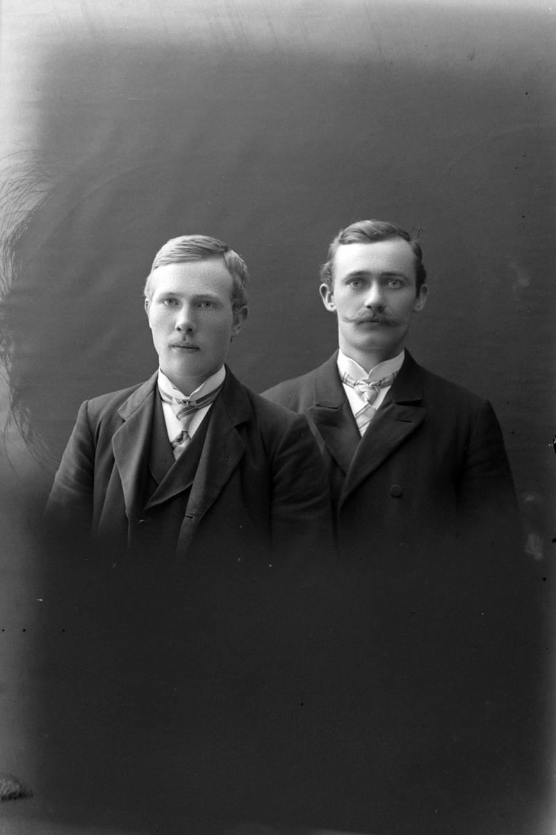 Studioportrett av to menn i halvfigur.