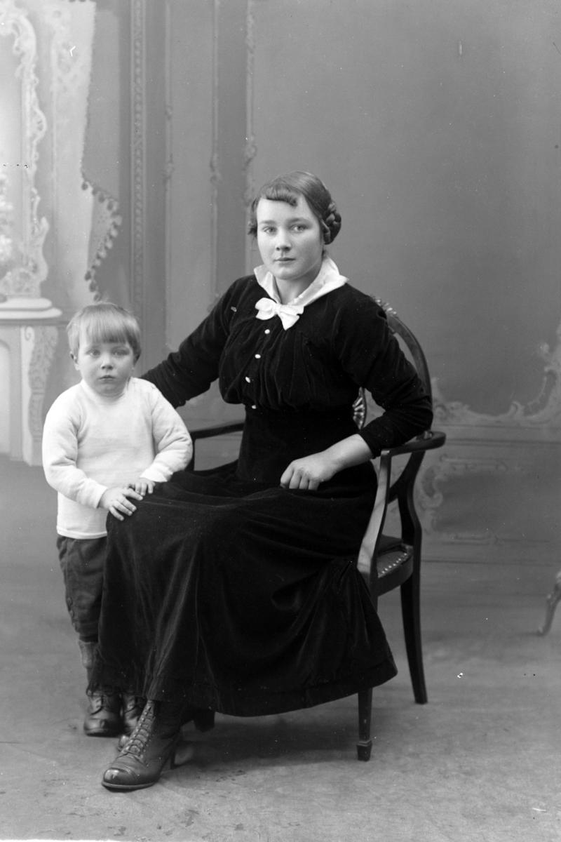 Studioportrett av en sittende kvinne med et barn.