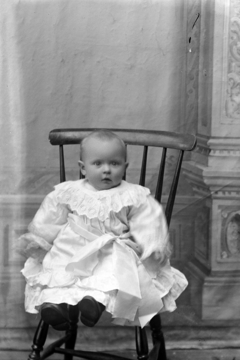Studioportrett av barn på en stol.