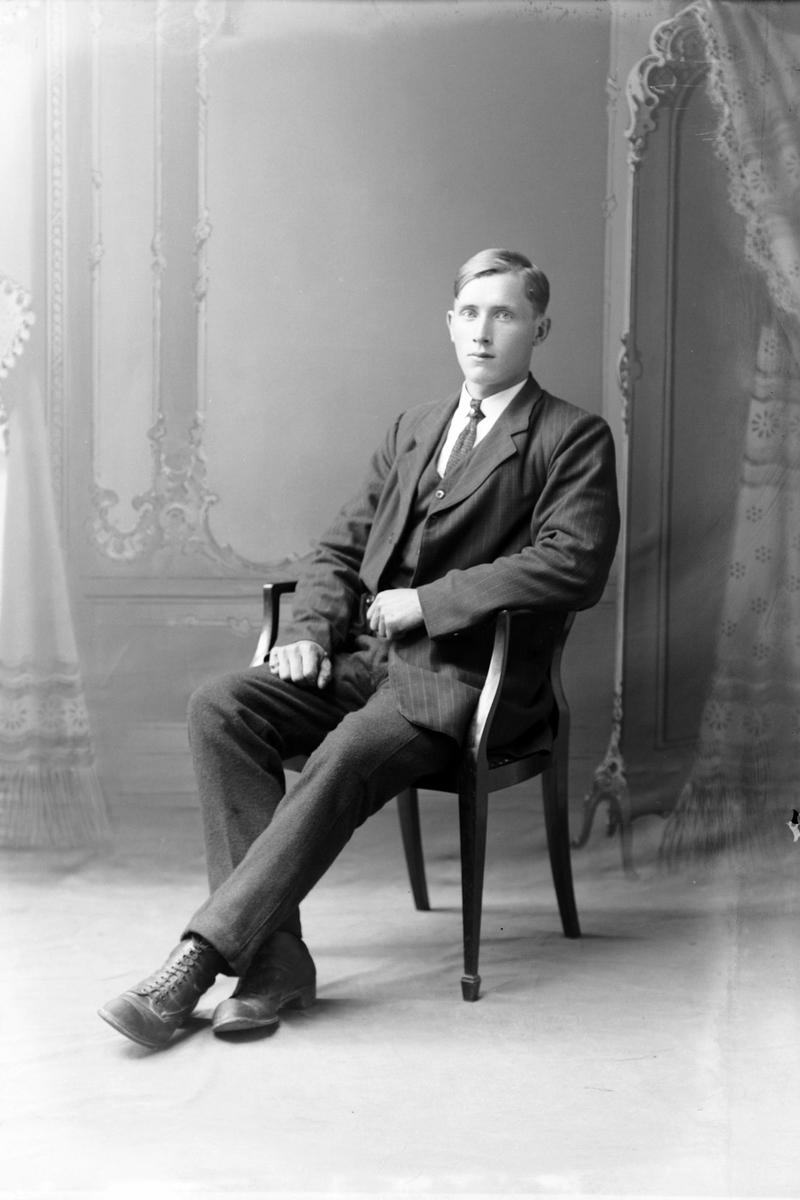Studioportrett av en mann som sitter.