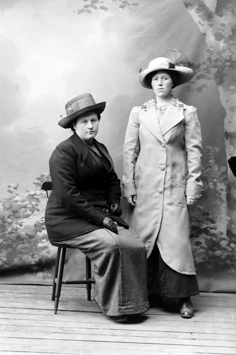 Studioportrett av to kvinner med frakk og hatt.