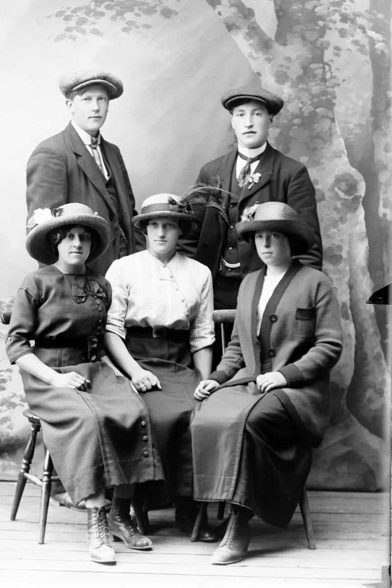 Studioportrett av tre kvinner sittende foran to menn som står.