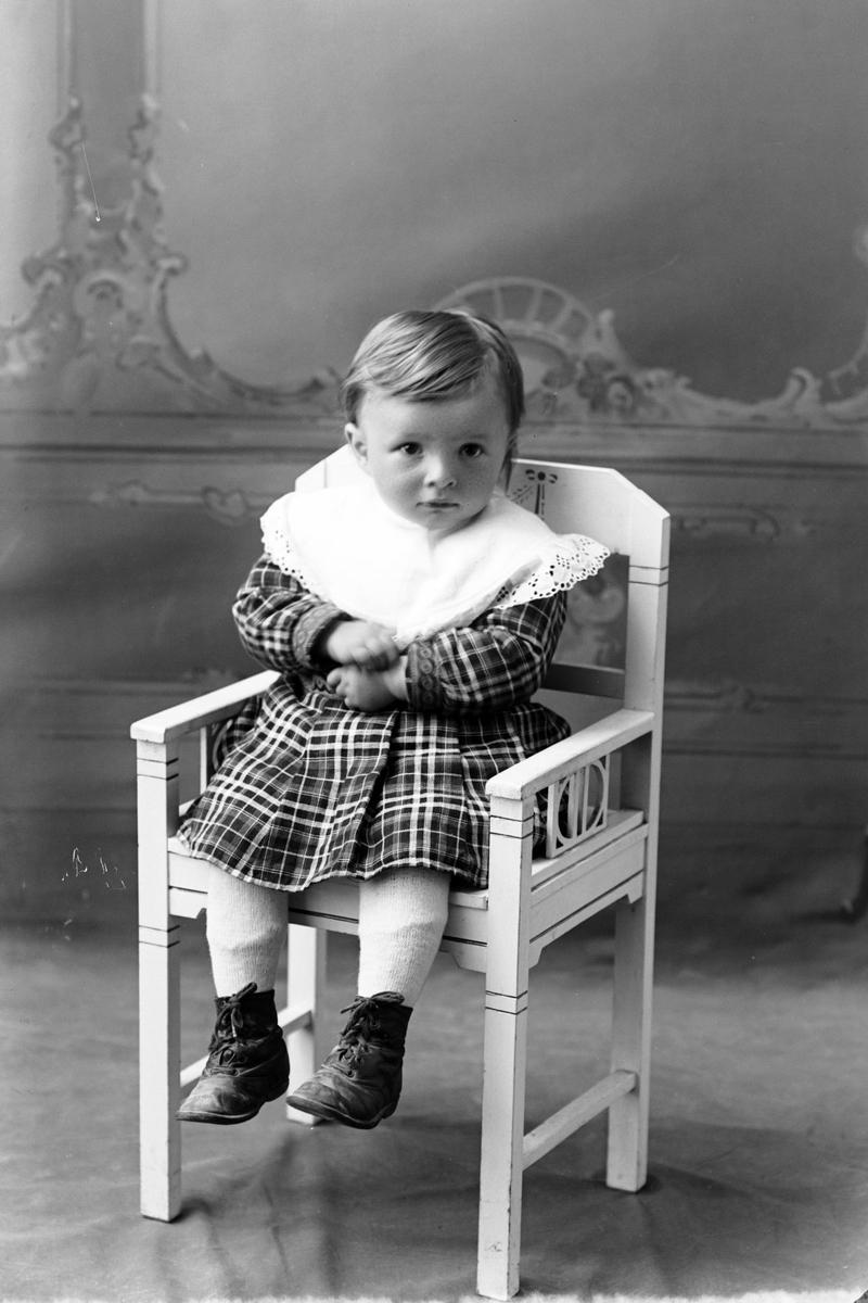 Studioportrett av et lite barn sittende på en hvit stol.