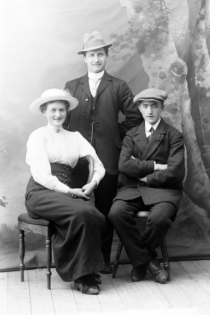 Studioportrett i helfigur av tre personer.