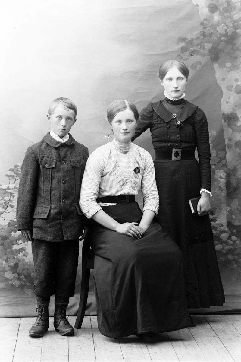 Studioportrett av tre personer i helfigur.