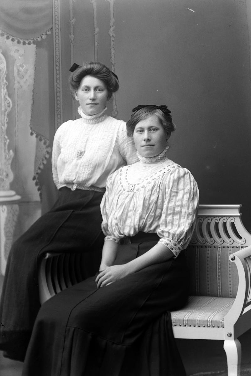 Studioportrett av to kvinner som sitter.