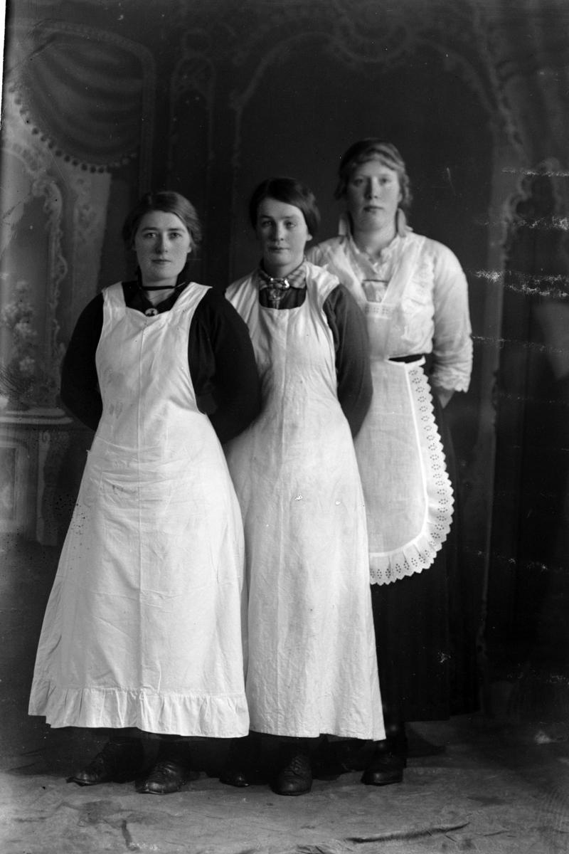 Studioportrett av tre kvinner som har på seg forklær.