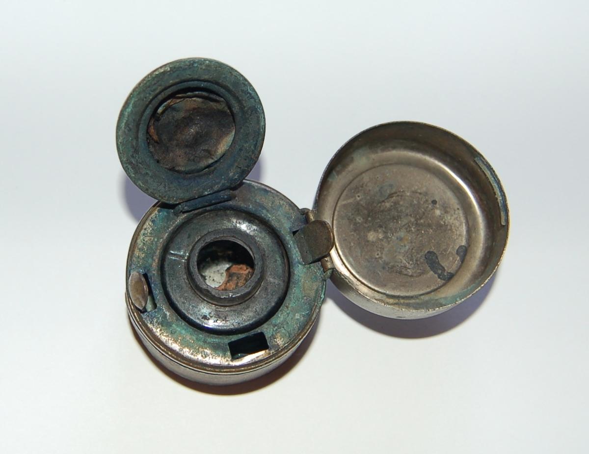 Sylindrisk metallbeholder, inneholdende en mindre glassbeholder. På metallbeholderen er der to lokk som er feste med hengsler. Eit mindre til lokk på glassbeholderen, og eit ytre som lukker det heile inne.