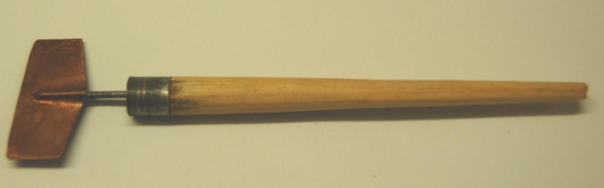 Liten skrapelignande gjenstand med skrapeblad av kopar, og med pennlignande handtak av tre.
