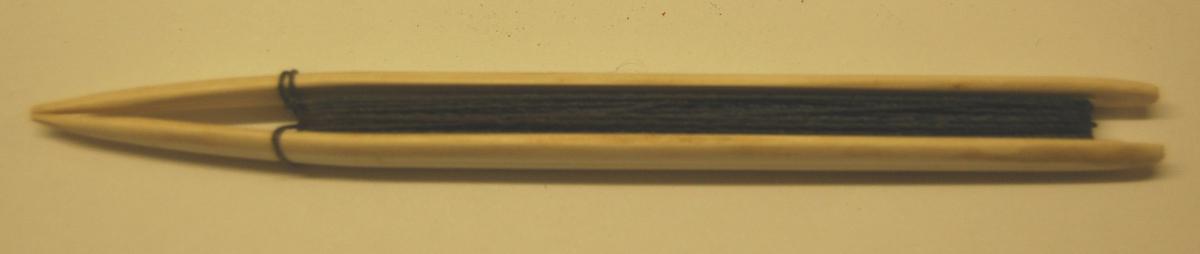 Garnbindingsnål av plast med rest av garntråd.