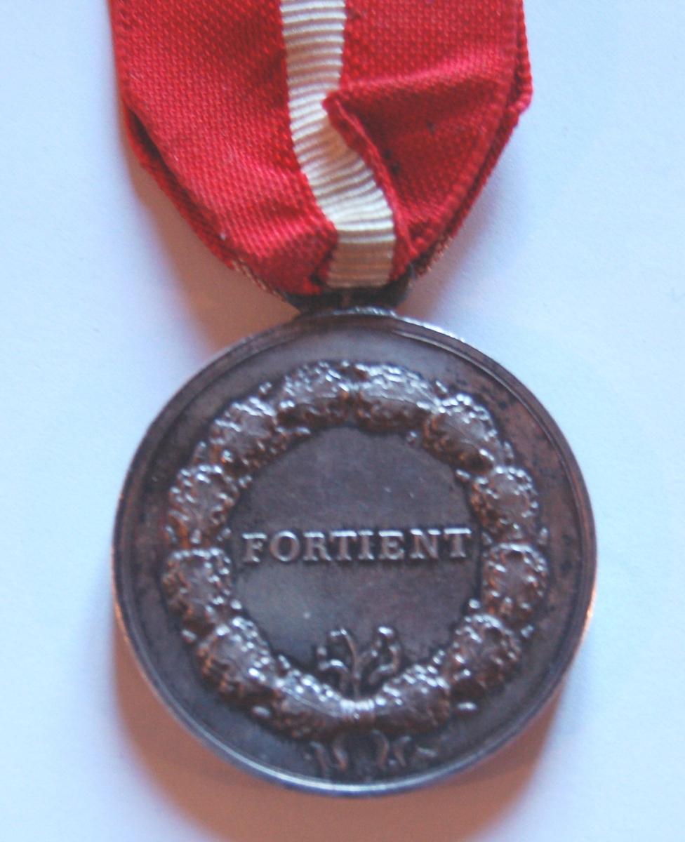 Rund medaljong med sløyfe med hvitt kors på rød bunn