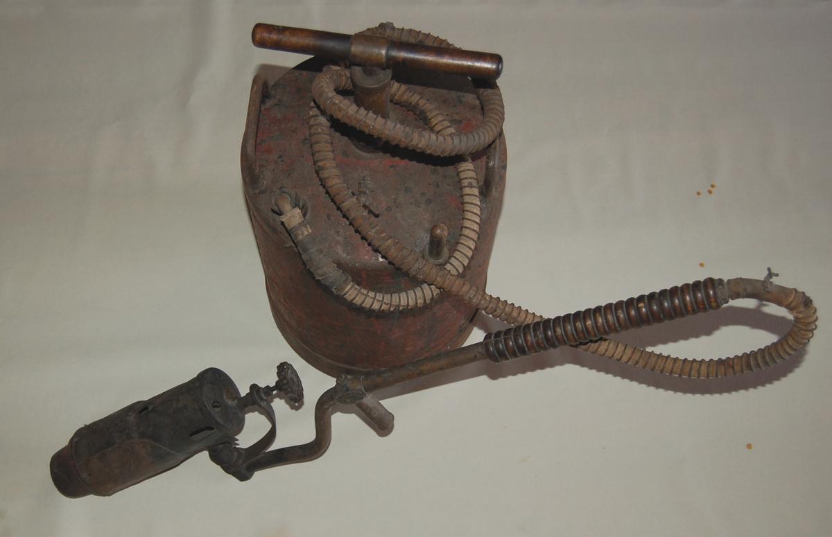 Parafinbrenneren er via en armert slange tilkoblet en kanne. På toppen av kanna er der en handpumpe for tilførsel av parafin til brenneren.