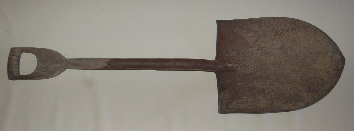 Spadebladet er breitt i formen, og festet til et forholdsvis langt skaft av tre.