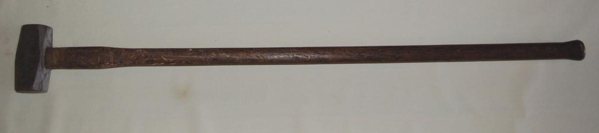 Sleggehammeren er av stål, og festet til et forholdsvis langt skaft av tre.