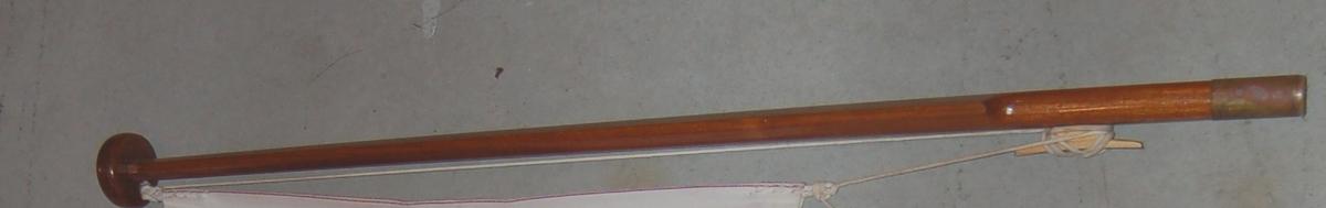 Elipseformet trestang med kule på toppen, og en rørformet messingholk i andre enden.