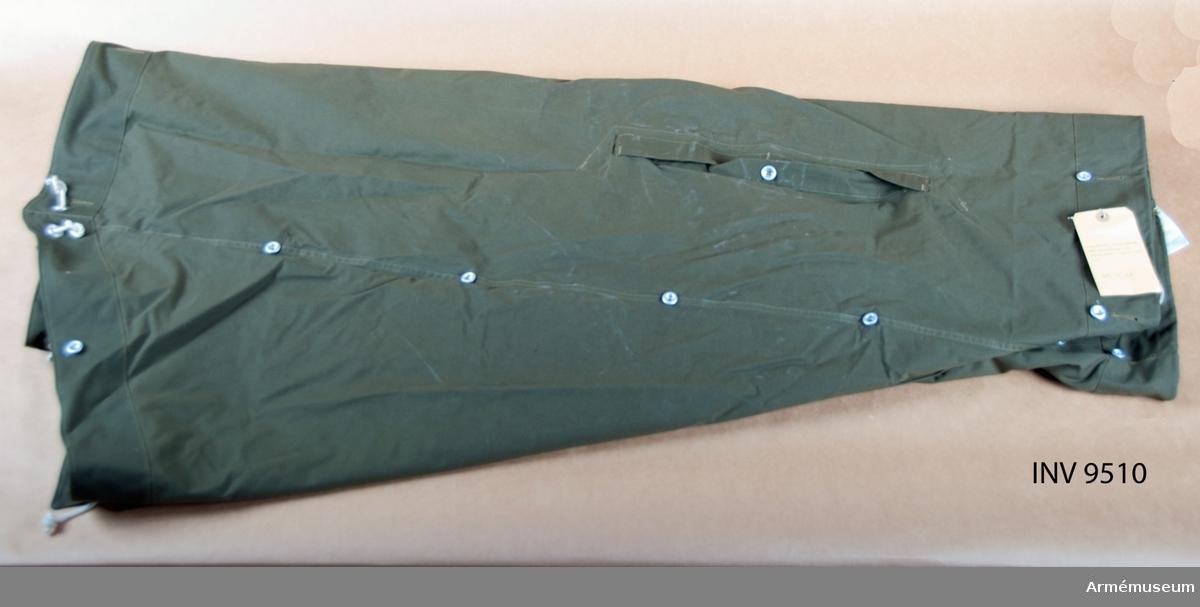 Regnskydd, utländsk försöksmodell med kapuschong och tältpinnar. Tillhörande fodral. Tillverkat av mörkgrönt impregnerat tyg..