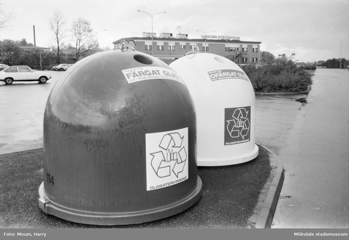 """Återvinningsbehållare för glas i Lindome centrum, år 1984. """"Gatukontoret har nu placerat ut dessa glas-igloos. Men de är enbart avsedda för glas. Annat material kan förstöra sändningarna till återvinningen.""""  För mer information om bilden se under tilläggsinformation."""