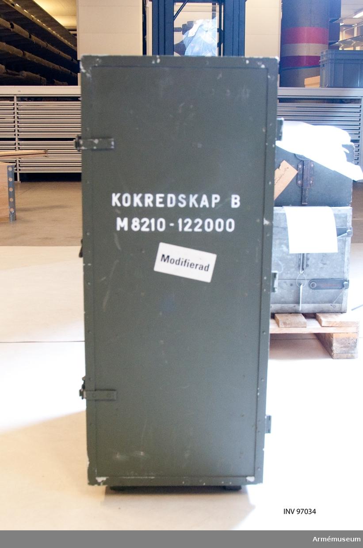 Kokredskap i grönt skåp innehållande lådor och fack.