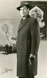 Mannekäng klädd i en mörkgrå överrock med dold knäppning. Sc