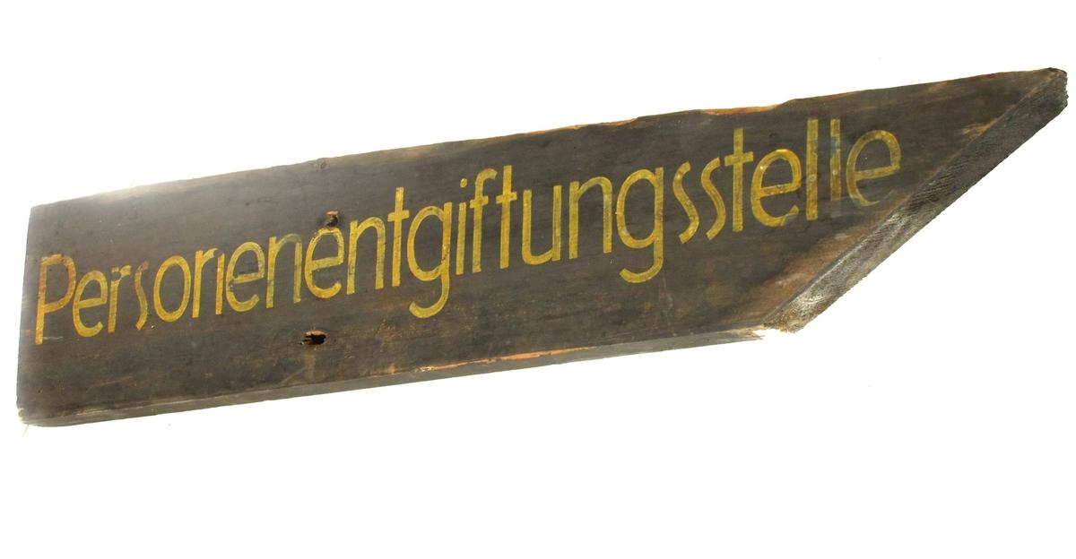 Skilt, av tre, med spiss ende på høyre side, malt i jordgrønn farge med gul tekst på tysk. Noe avbrukket i øvre side.