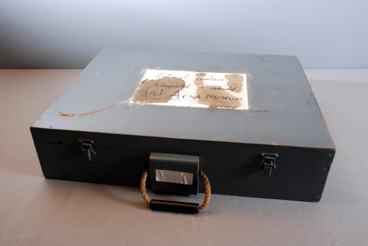 Koffert for linepistol/redningspistol med raketter, patroner og bruksanvisning. I kofferten er det også en flaske med olje. Kofferten er rektkangelformet med lokk og bunn. Håndtak på midten og to låser på hver side av håndtaket. Laget av hamp med plastrør tredd på. Lokket er hengslet i bakkant og har stopper av bomullsbånd på ene siden. Linepistolen og utstyret ligger løst nedi kofferten. På innsiden av lokket er festet bruksanvisning.
