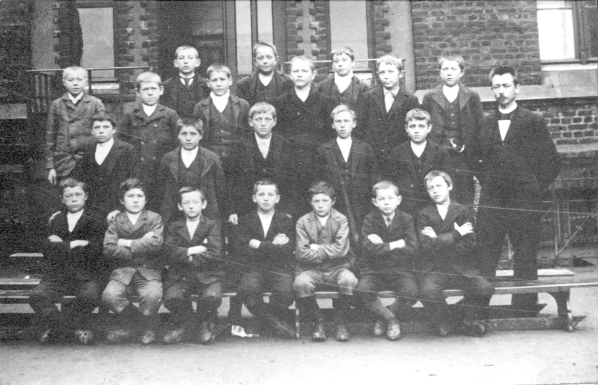 Gruppebilde - 21 gutter og deres lærer i skolegården på Breidablik.k