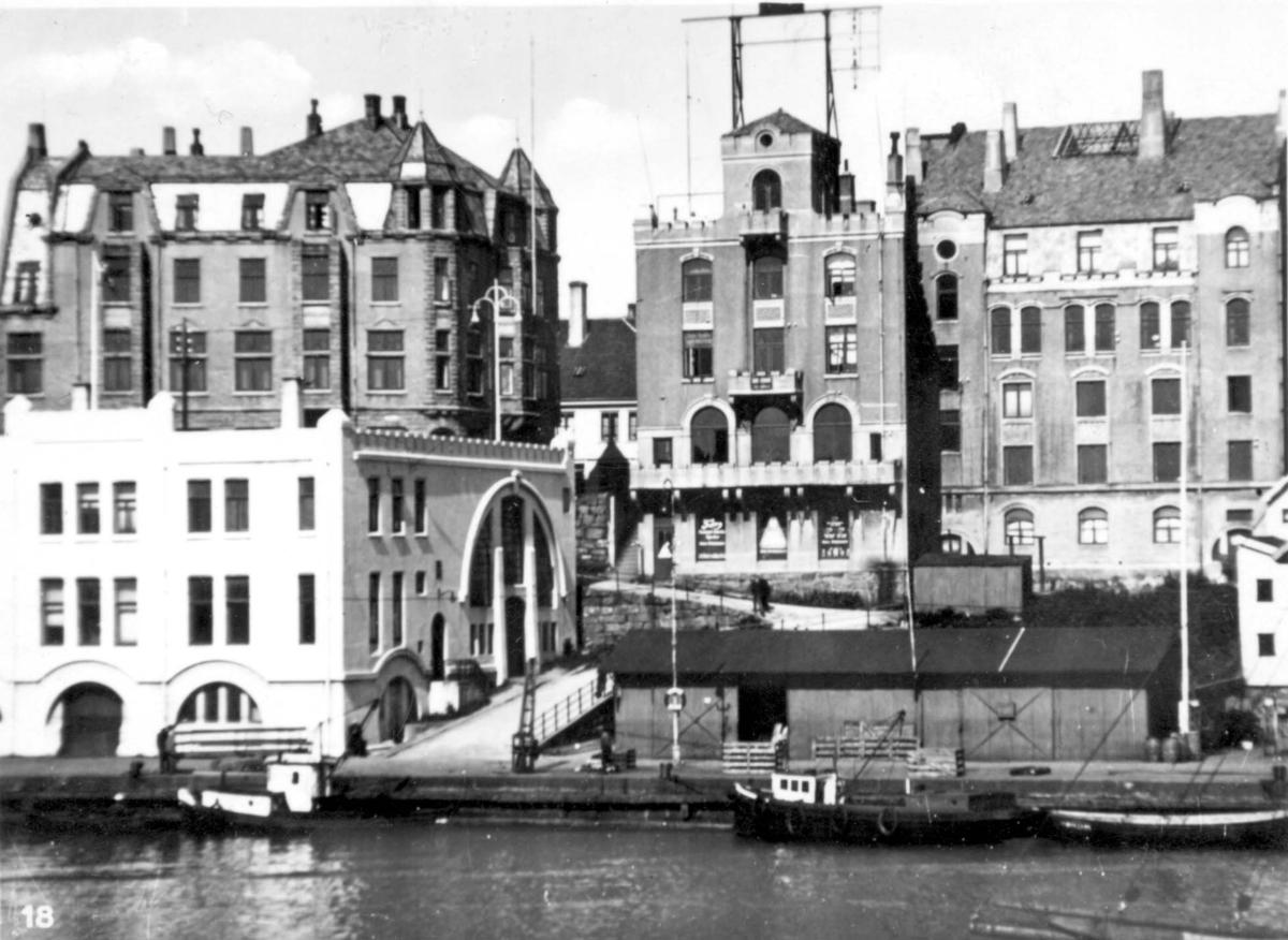 Det hvite huset i forgrunnen er den gamle tollboden, bak det Handelstanden, videre mot høyre Skipperforeningen og bygget der Torvastadbanken holder til.