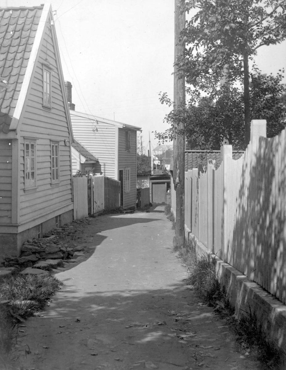 """Parti fra Tollbodgaten, sett sørfra. Kan det være Hasseløy og """"Stålehuset"""" vi skimter i bakgrunnen? Trang gate eller smug med små trehus på hver side. Nærmest på høyre side et plankegjerde og en hage. Huset til venstre ser ut til å være fra omkr. 1850 - 60 årene."""