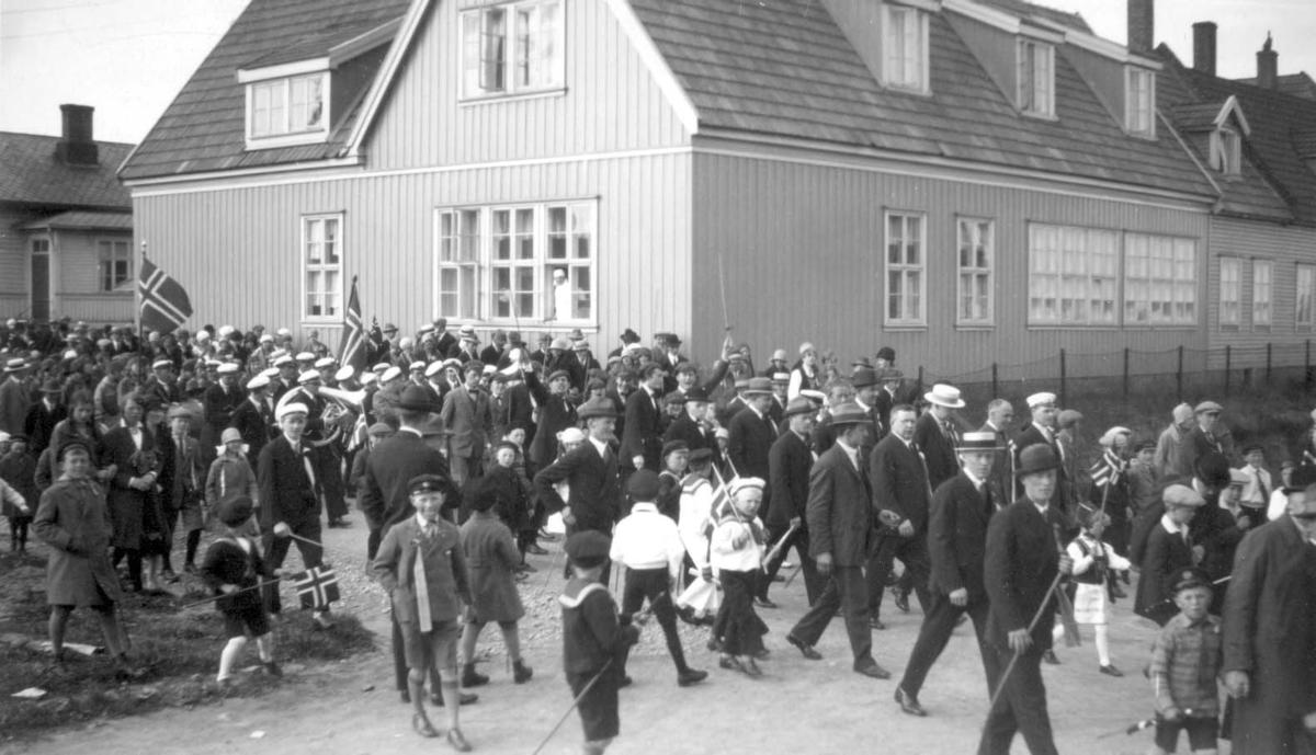 """Russetoget på vei ut fra Havnaberg skole en 17. mai i 1920-årene. Denne gang er det bla.annet skipsreder Sunfør som er karikert på en plakat med teksten: """"Sunfør har forskrevet sig""""."""