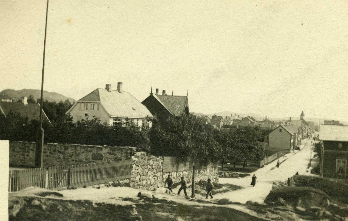 Gateparti sett fra Havnaberg og sørover i Strandgaten. Bildet viser til v. skolegården på havnaberg Middelskole, og O.M. Christiansens hus. Til h. ses bøkkermester O. Hamres hus. I bakrunnen ses DBH-huset. Bakerst i bildet ser en tårnet på Rådhuset (senere Politikammeret).